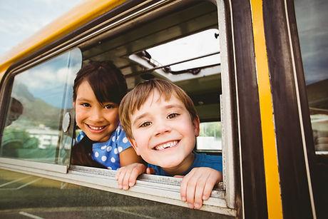 cute-pupils-smiling-camera-school-bus.jp