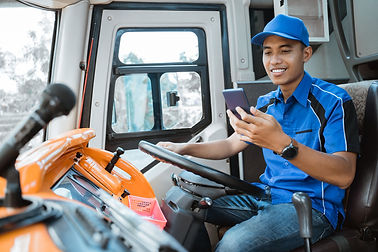 male-driver-uniform-looks-his-cellphone-while-holding-wheel-bus.jpg