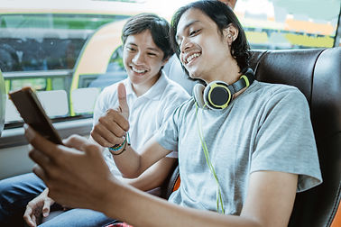 young-asian-man-with-headphones-using-mobile-phone-video-calls-with-thumbs-up-while-sittin