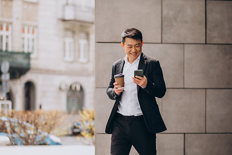 young-handsome-asian-business-man-black-suit-using-phone-drinking-coffee.jpg