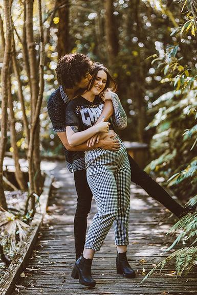 Couple cuddle up on jungle walk, boyfriend kisses girlfriends cheek