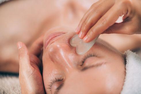 Guasha face massage with jade stone. Clo
