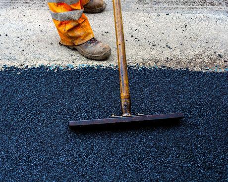Worker on Asphalting paver machine durin