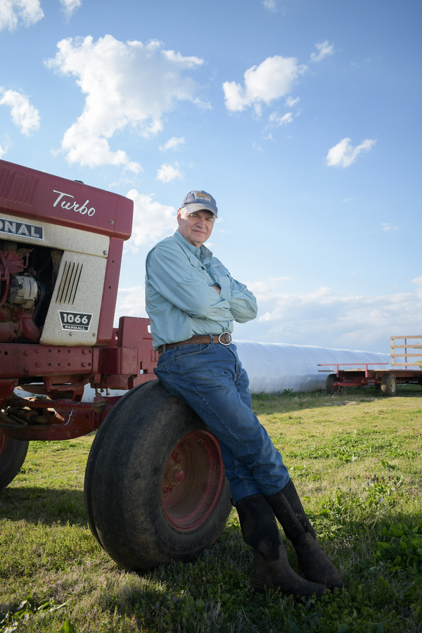 Carl Neal Chaney poses up against a tractor. Carl's father James Riley Chaney started milking his own herd of cows in 1942 and sold the farm to Carl in 1985. Carl and his niece Dore Baker opened Chaney's Dairy Barn, the tourism side of the business, in 2016.