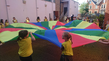 Having fun in the shul courtyard with co-operative parachute games