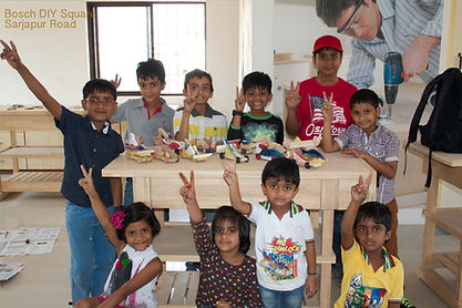 Kids posing with the wooden toy cars they built during a birthday party