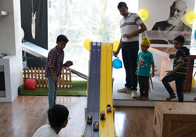 Kids playing with the wooden toy cars they built during a birthday party