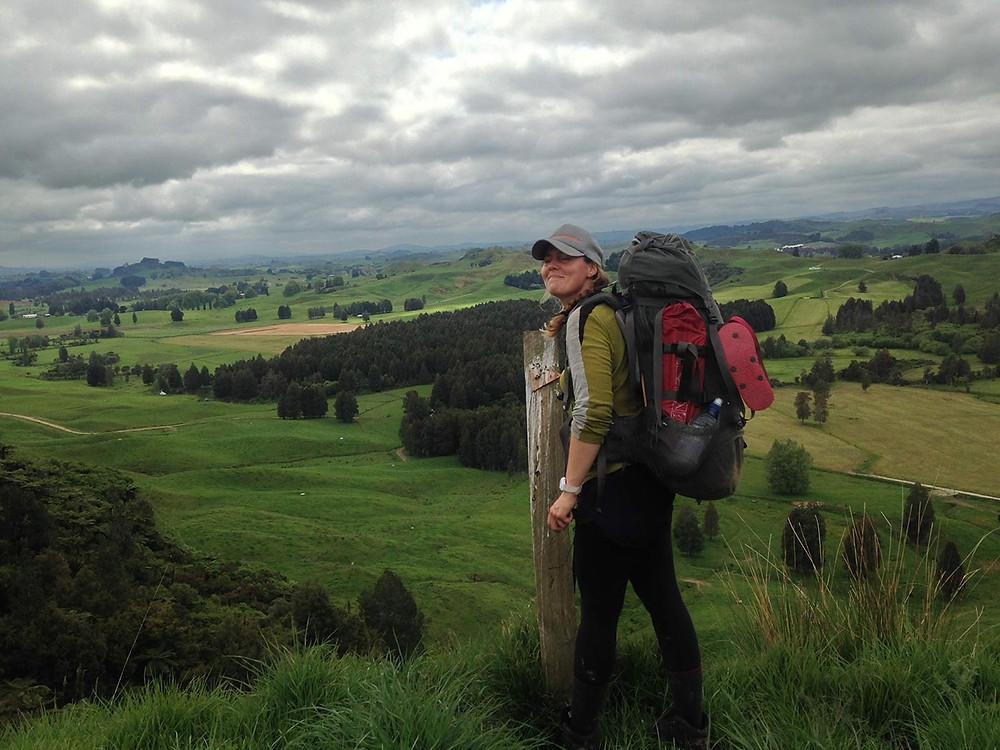 Wanderin auf dem Te Araroa Trail in Neuseeland auf grünem Hügel