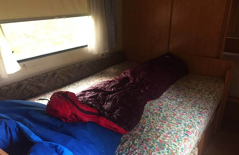Augebreiteter Schlafsack auf Matratze in einem Campervan
