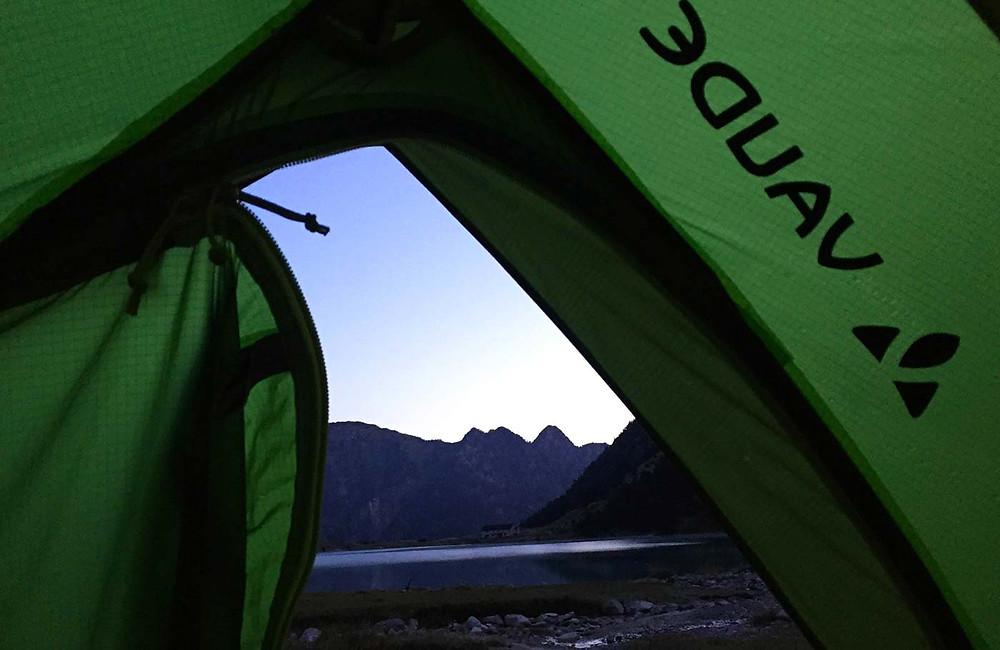 Sicht aus halb geöffneten Zelt auf Bergsee