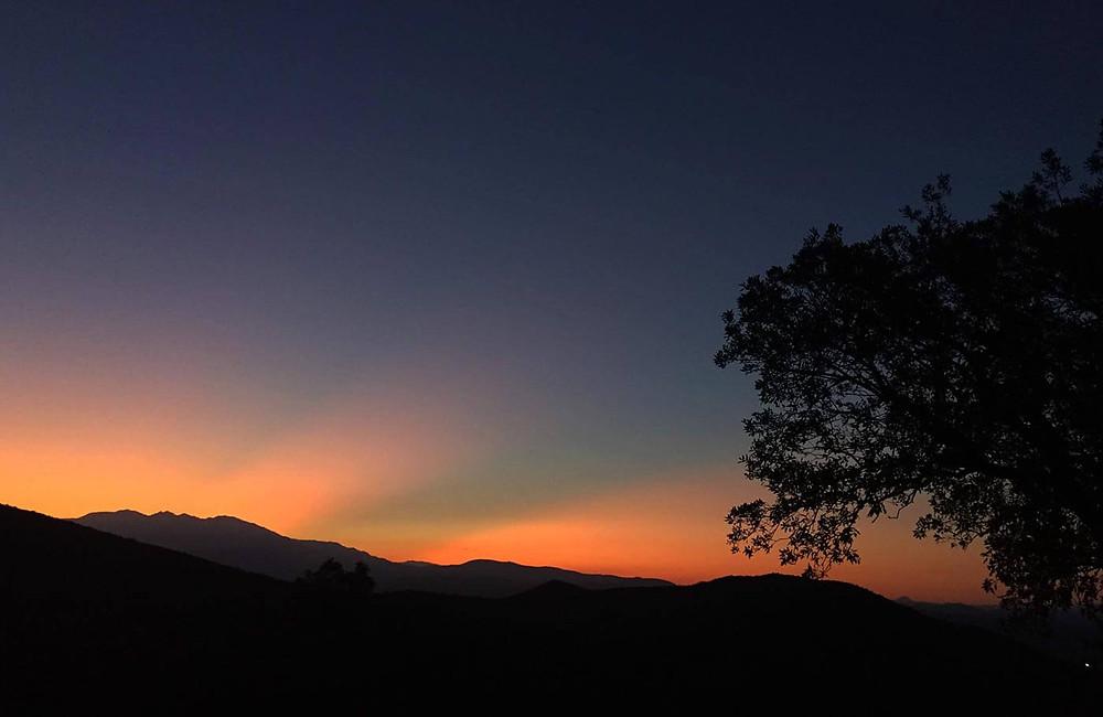 Lila-Organge farbiger Sonnenuntergang mit Bergen im Hintergrund