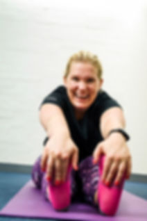 Personal Trainer Hannah Nordlund is stretching and laughing wearing happy colors