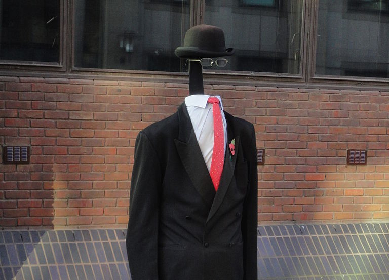 Invisible person wearing a black masculine suit with red tie, black bowler hat and glasses