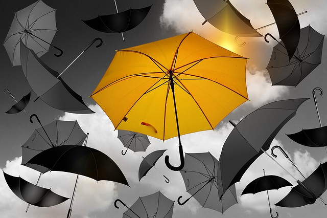 Black and white umbrellas flying in the air, one full colour yellow umbrella
