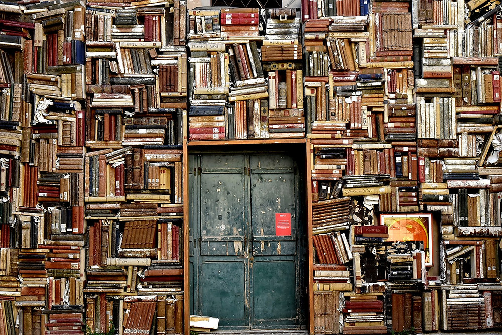 A dilapidated, locked door surrounded on all sides with piles of precariously balanced books