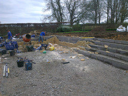 Dry stone wall cladding being installed