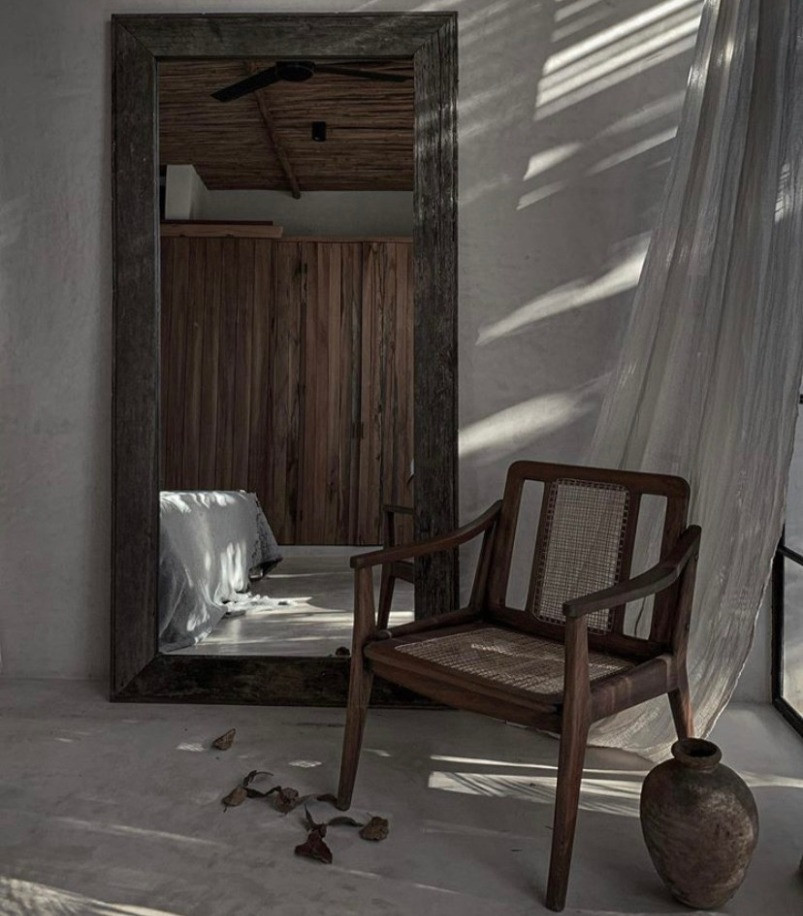 This image displays a mirror crafted with ancient wood, as well as an up-cycled chair from the past and an old vase.