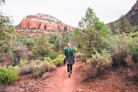 Girl hiking towards devil's bridge Sedona desert