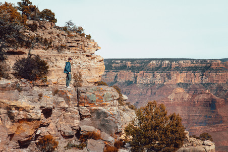 guy looking inside grand canyon on edge of cliff