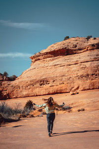 girl with wind in hair on orange rocks