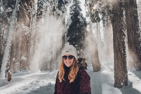 portrait of girl with hat and sunglasses in snow forest