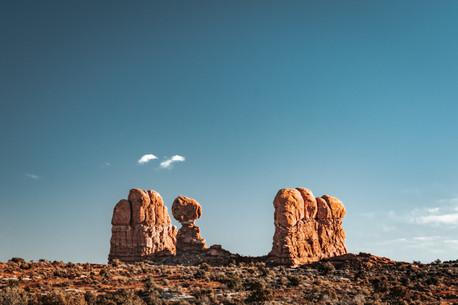 balancing rock formation blue sky desert landscape