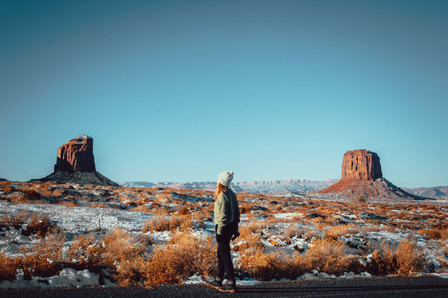 Girl in monument valley winter snow blue sky