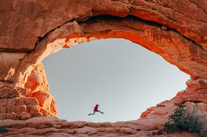 guy jumping inside stone arch utah adventure photo