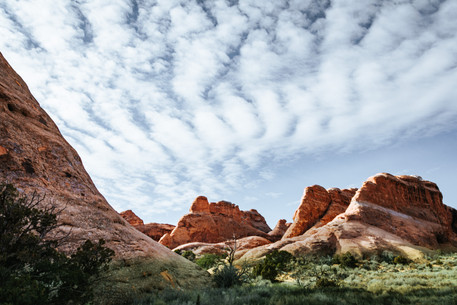 clouds and orange rock formation arches utah