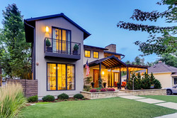 Custom home modern front with balcony and front terraced courtyard.