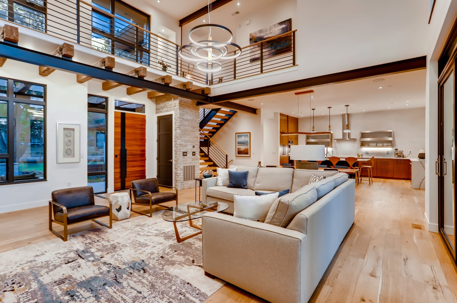 Great room with connecting bridge above and Kitchen beyond.