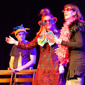 Image Description: Michel, Laura and Karen dressed up in hats and sunglasses on stage perfoming in Love Me.