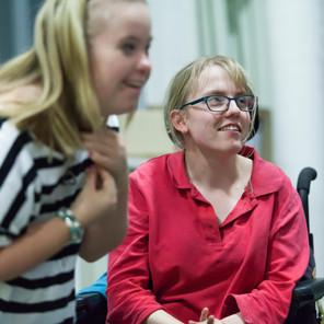 Image Description: 2 workshop participants smiling whilst perfoming in the workshop.