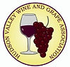 "Image of glass of red wine with red grape cluster next to it, encircled by the smaller print of ""Hudson Valley Wine & Grape Association"""