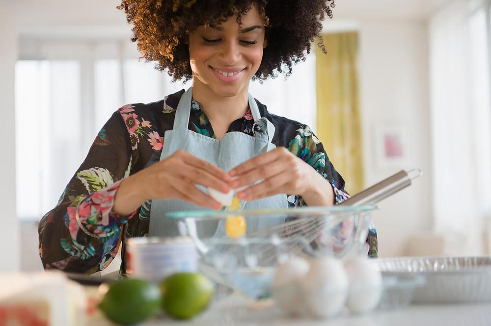 Mulher cozinhando Safanelli Eletrodomésticos.