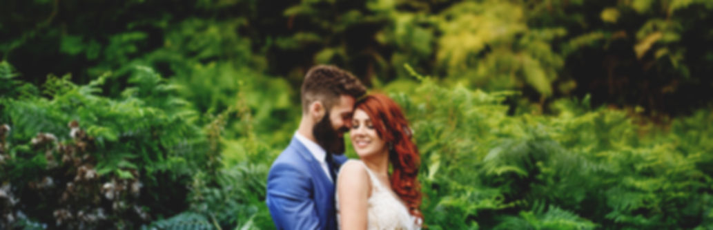 bearded Groom with redhead bride amongst the fern of a woodland wedding at The Keeper and the Dell