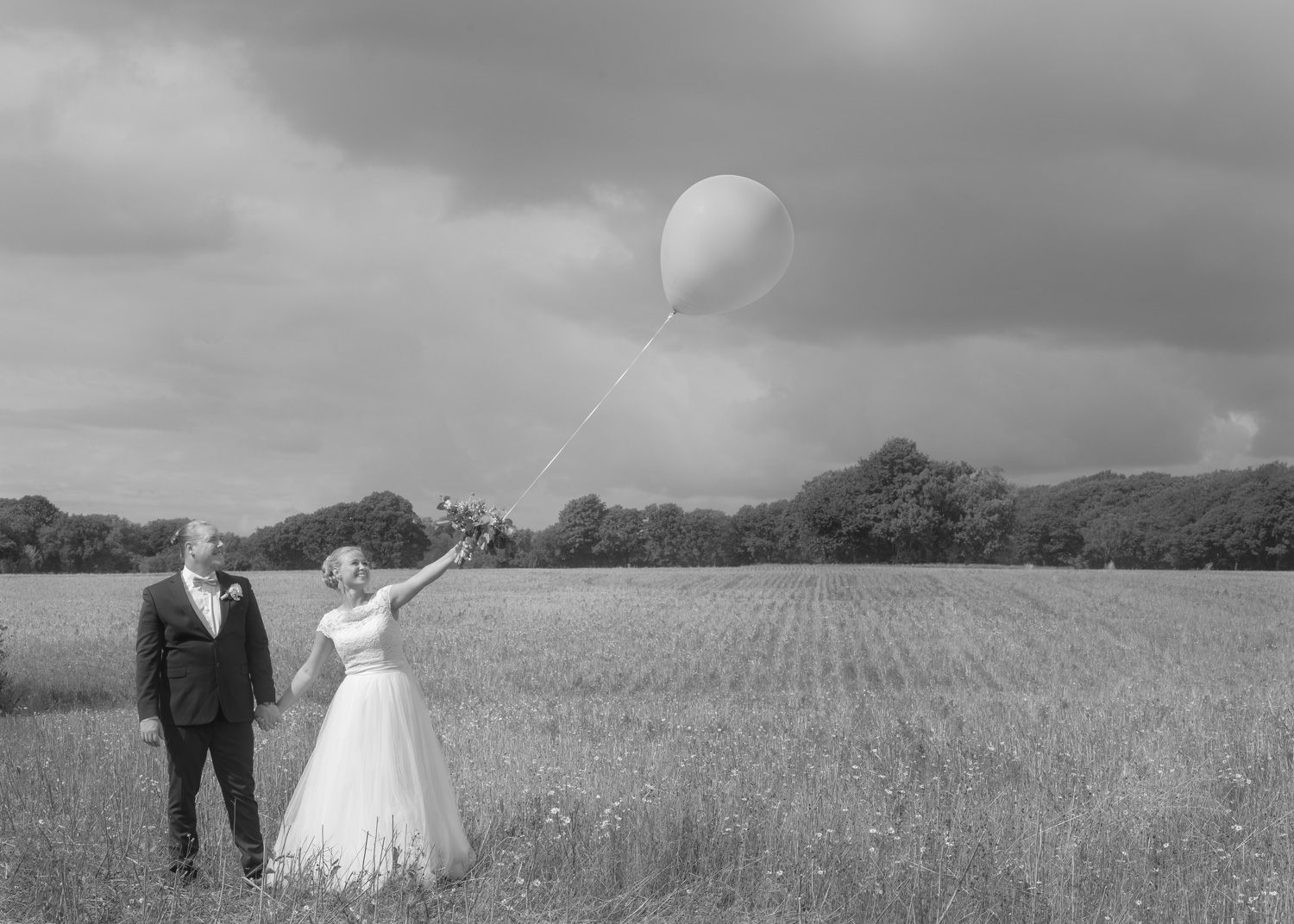 bride & groom on field with balloon