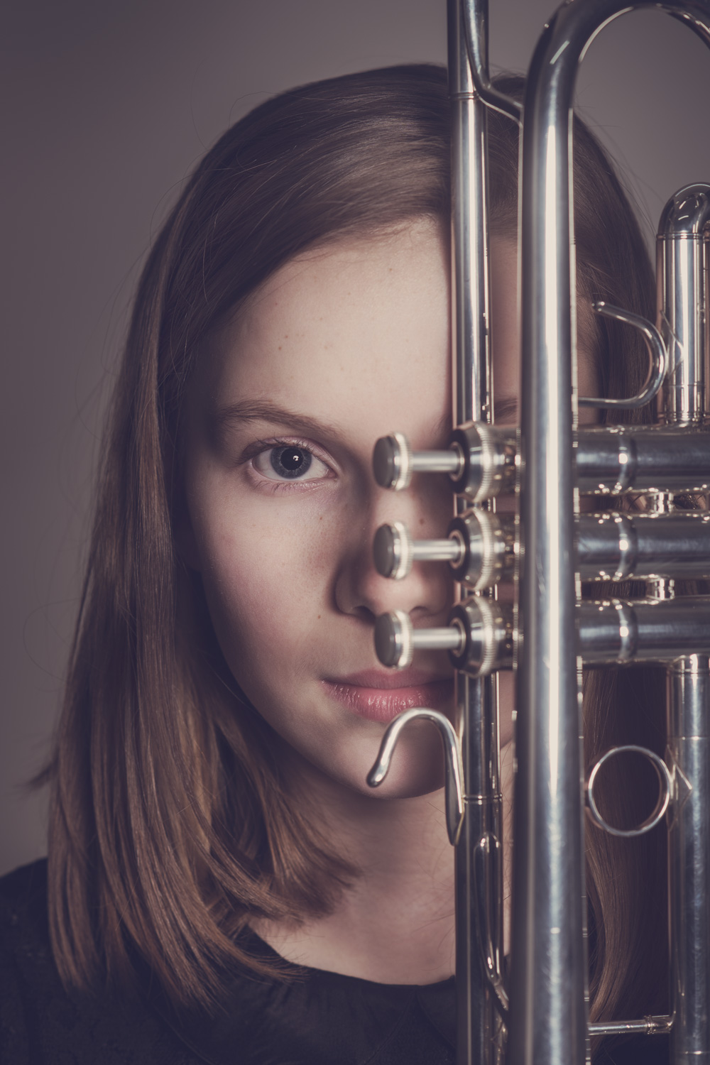 Studio portrait of girl & trumpet.