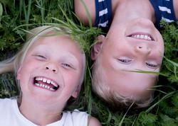 Barnfoto tvillingar i gräset