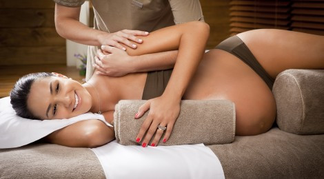 A pregnant lady looking happy and supported having her pregnancy massage