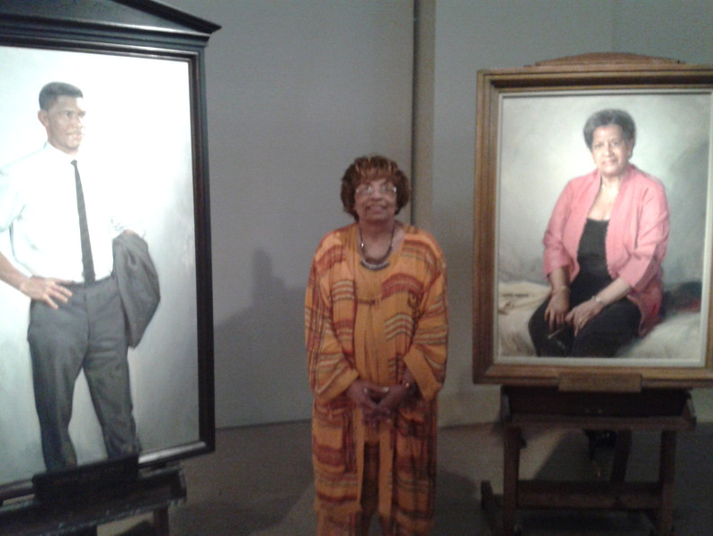 Flonzie pictured between the photos of Medgar and Myrlie Evers.