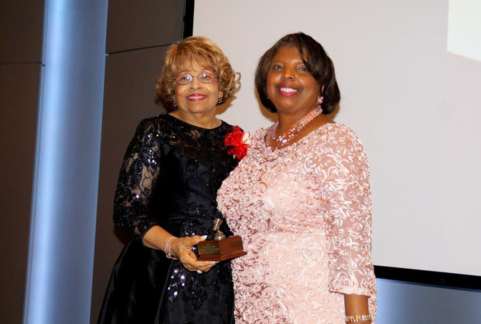 Angela Stewart, Vice-President of Women for Progress presents an award to Flonzie in recognition of the 50th anniversary of her 1968 election.