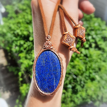 oval shaped lapis lazuli pendant wrapped in brown suede and copper wire displayed on wrist with trees in background