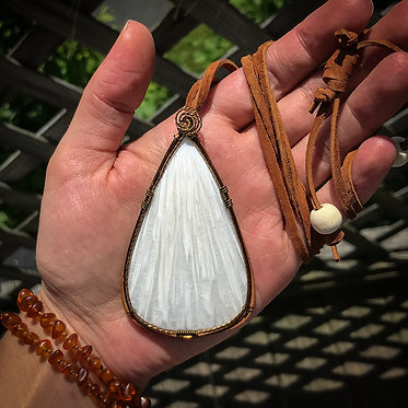 large teardrop shaped Scolecite pendant displayed on palm of woman's hand