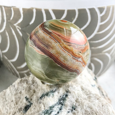 45mm green banded calcite crystal sphere with swirls and bands of green, brown, tan, and red earth tones