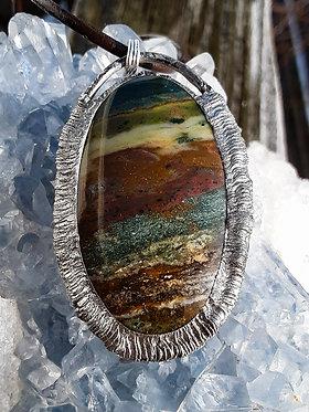 earth toned oval banded ocean jasper pendant encased in a textured silver solder setting
