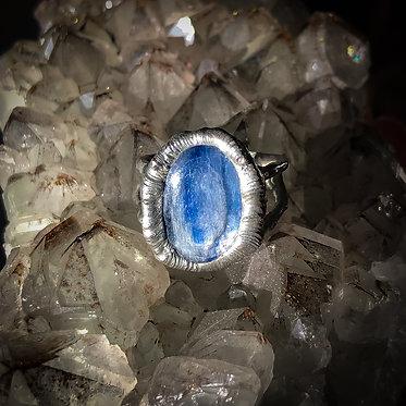 polished blue kyanite handmade ring resting on smoky quartz