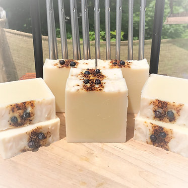 handmade bars of soap displayed on wooden cutting board with windchimes and trees in the background