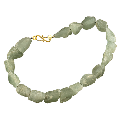 A strand of raw green aquamarine stones with a 18 karat gold s clasp