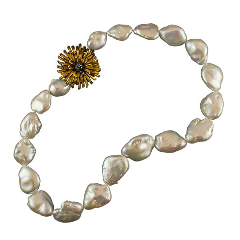 A strand of baroque pearls with a gold and silver chrysanthemum clasp
